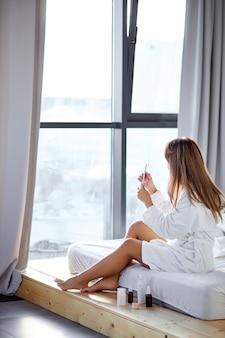 Vista laterale sulla giovane donna in accappatoio limando le unghie in camera da letto luminosa, nei fine settimana. donna dopo la doccia a casa a causa dell'epidemia di coronavirus. vita domestica