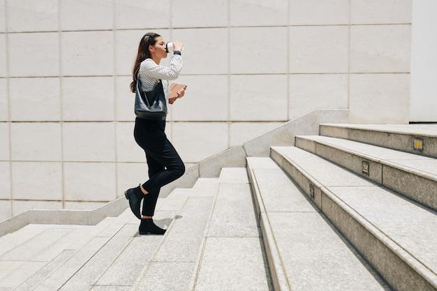 Vista laterale del giovane imprenditore femminile con tavoletta digitale salendo le scale e bevendo caffè da asporto