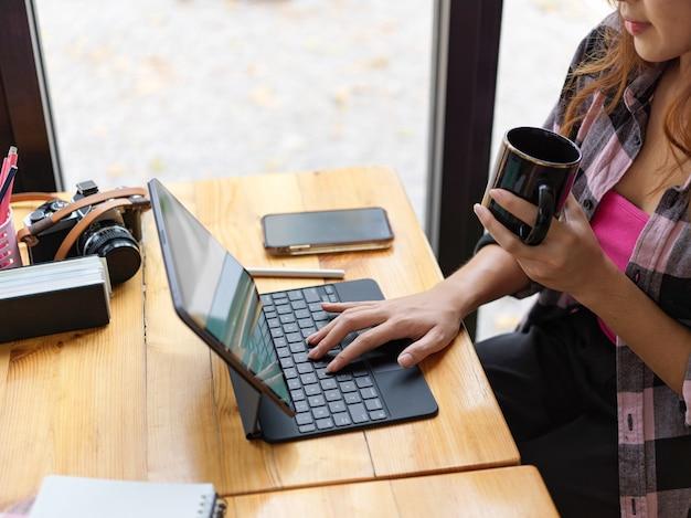 Vista laterale della giovane femmina libero professionista che tiene tazza di caffè e lavora con tavoletta digitale sulla tavola di legno nella caffetteria