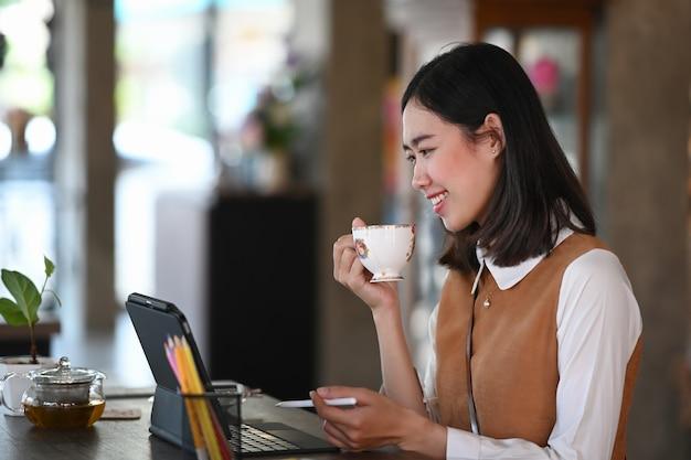 Vista laterale della giovane donna seduta nella caffetteria lavorando con tablet computer