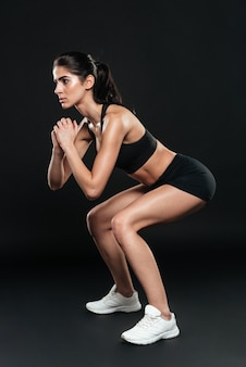 Vista laterale di una giovane donna in forma che fa squat su un muro nero