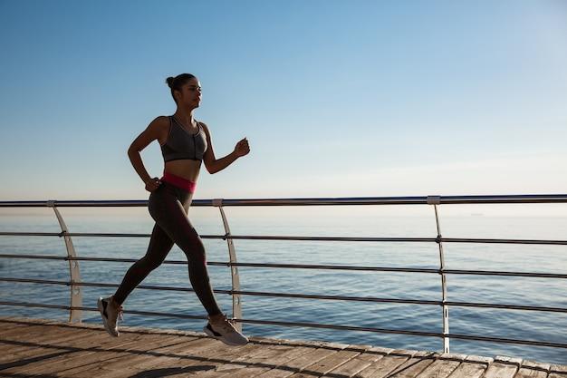 Vista laterale della giovane donna fitness che corre lungo il molo.