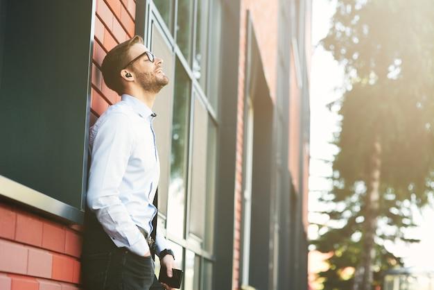 Vista laterale di un giovane uomo d'affari felice che ascolta musica con auricolari wireless e telefono cellulare