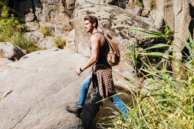 Vista laterale di un giovane che esplora il deserto su un'avventura di trekking