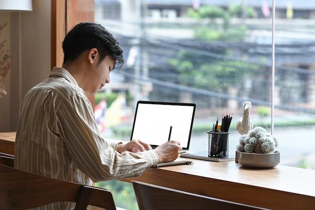Giovane di vista laterale che si siede davanti al computer portatile al caffè e che prende appunti sul taccuino.