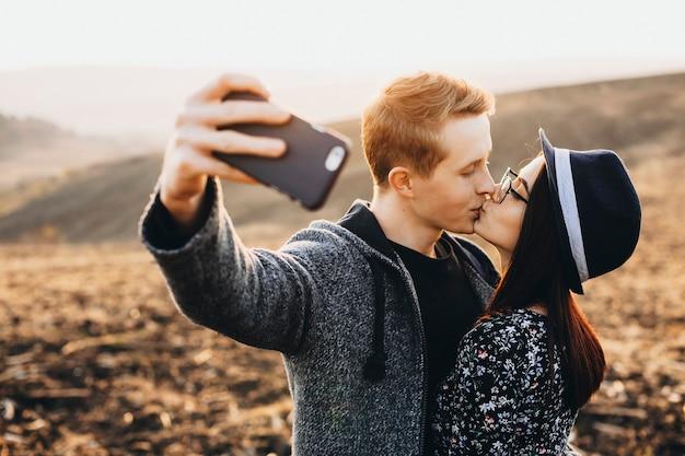 Vista laterale del giovane uomo e donna che tengono gli occhi chiusi e si baciano mentre posa per selfie sullo sfondo di una campagna incredibile.coppia baci e prendendo selfie in campagna