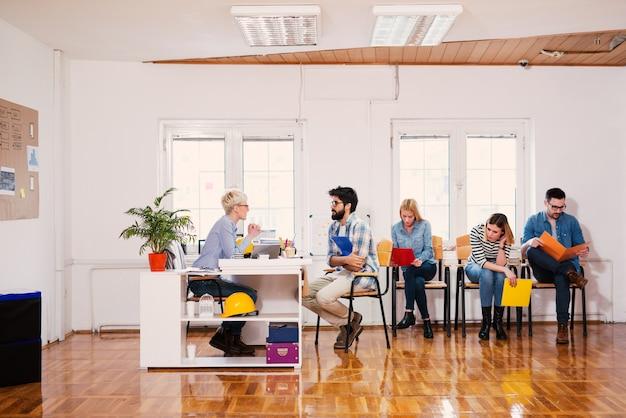 Vista laterale di giovani seduti in un ufficio e in attesa del colloquio di lavoro.
