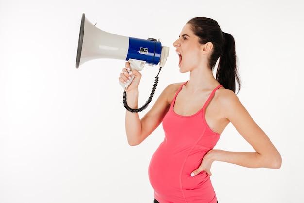 Vista laterale di una giovane donna incinta che grida in megafono