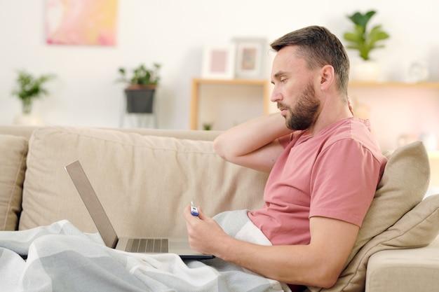 Vista laterale del giovane malato con termometro seduto sul divano sotto la coperta, toccando il collo e consultando un medico online davanti al laptop