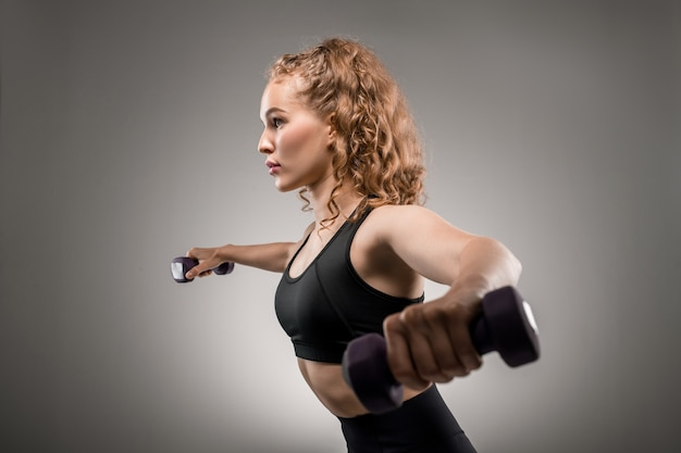 Vista laterale della giovane sportiva in tuta nera sollevamento manubri e respirazione durante l'esercizio fisico su grigio