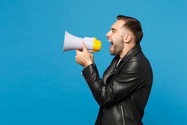 Vista laterale giovane uomo con la barba lunga in giacca nera t-shirt bianca urlare nel megafono, annuncia la vendita di sconti isolata sul ritratto in studio di sfondo muro blu. concetto di stile di vita della gente. mock up copia spazio.