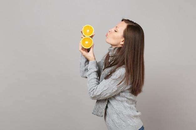 Vista laterale della giovane donna in maglione, sciarpa che soffia mandando un bacio d'aria alle arance isolate su sfondo grigio. stile di vita sano, persone sincere emozioni, concetto di stagione fredda. mock up copia spazio.