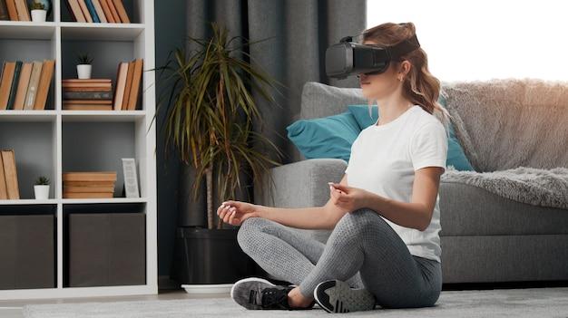 Vista laterale della giovane donna che utilizza ar mentre medita seduto nella posizione del loto sul pavimento al chiuso
