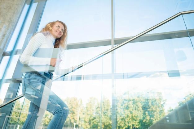 Donna di affari laterale che cammina su per le scale