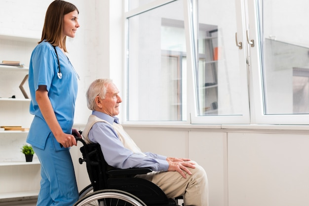 Vecchio lateralmente seduto sulla sedia a rotelle