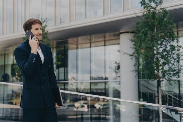Colpo laterale di un uomo barbuto che chiama tramite smartphone vestito con un abito formale nero posa all'aperto