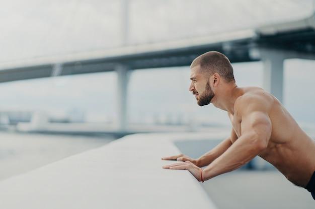 Colpo laterale di bell'uomo muscoloso con folta barba fa push up esercizio ha allenamento all'aperto si appoggia sul recinto del ponte impegnato in pose di attività fisica con il torso nudo ha muscoli forti