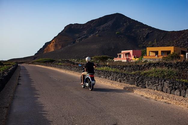 Il giro turistico in scooter sullo sfondo il monte nero famoso vulcano di linosa
