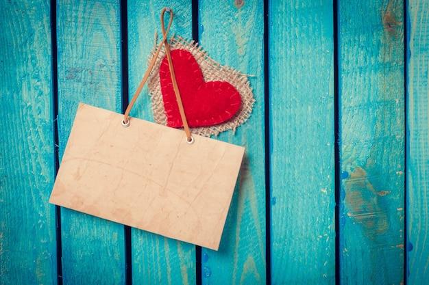 Cartello, cuore d'amore, appeso su sfondo di legno vintage