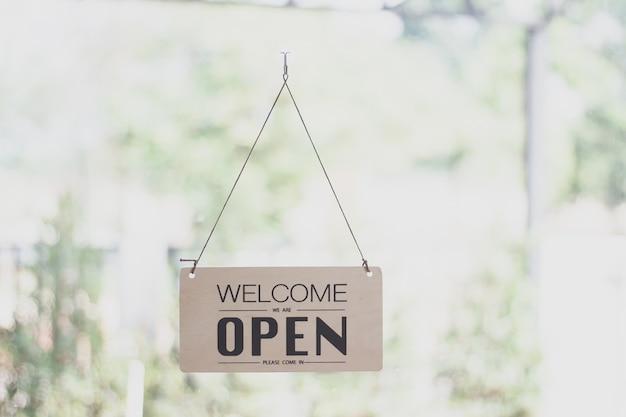 Un segno che appende fuori dalla caffetteria, segno aperto sfocatura sfondo, etichetta parola aperta