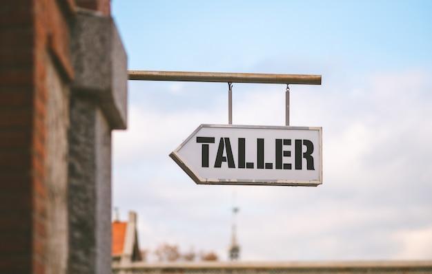 Cartello appeso in strada che indica che c'è un'officina meccanica con la parola spagnola più alta in una giornata di sole