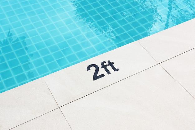 Segno che mostra la profondità del primo piano estremo della piscina.