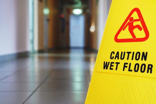 Un cartello che dice attenzione è un lungo corridoio industriale vuoto
