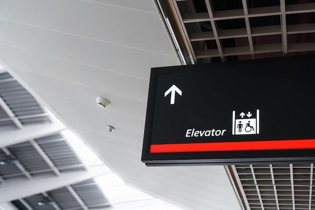 Un cartello con una freccia che indica l'ascensore nel terminal di attesa dell'aeroporto.
