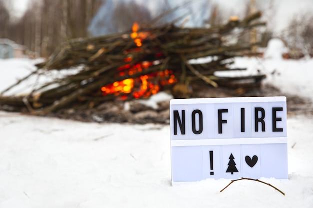 Un cartello con il testo nessun fuoco sullo sfondo di un grande incendio ardente