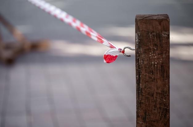 Nastro rosso-bianco di segnale legato ad un gancio su un palo di legno.