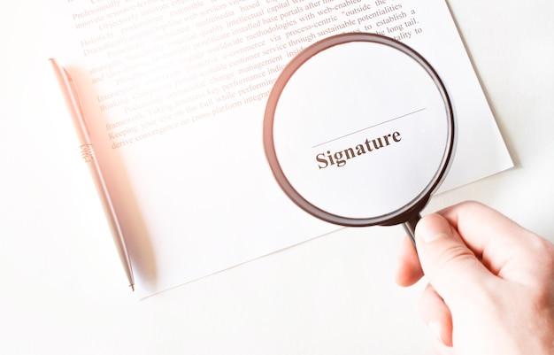 Linea signaure in contratto con penna e lente d'ingrandimento