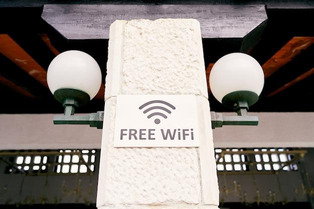 Insegna con un'iscrizione su un pilastro di pietra con iscrizione di lanterne wifi gratuito