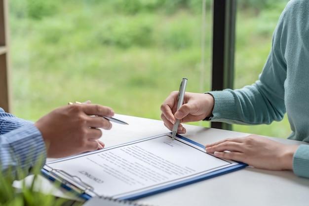 Firma di documenti contrattuali in collaborazione di uomini d'affari che accettano di fare affari in ufficio.