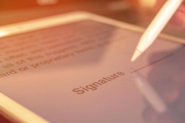 Firma del contratto con firma digitale sul tablet, primo piano del documento, stilo in mano, foto di messa a fuoco selettiva