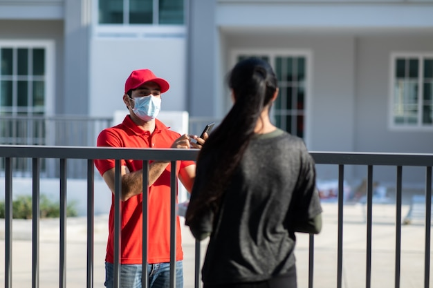 Firma della firma sul dispositivo smart phone per ottenere un pacchetto. donna che riceve pacchetto da fattorino in uniforme rossa