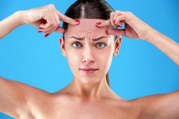 Segni di invecchiamento ritratto di giovane donna scioccata guardando con disappunto mentre si tocca le rughe sulla fronte sulla parete blu
