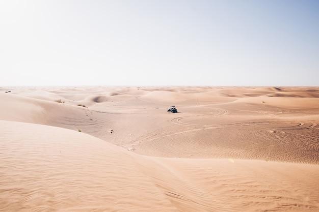 Silenzioso paesaggio desertico con guida quad buggy, dune di sabbia di al awir, dubai, emirati arabi uniti