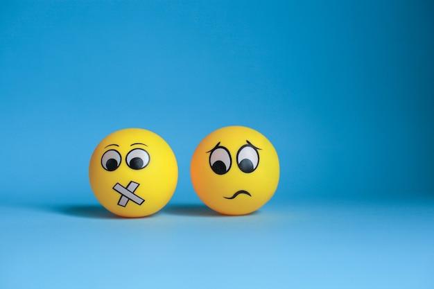 Faccia silenziosa e emoticon confuso su sfondo blu