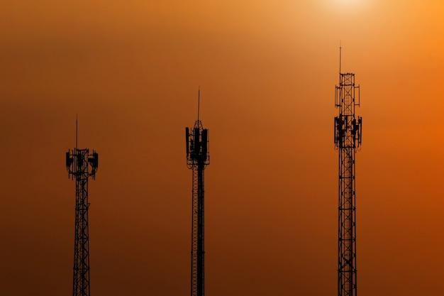 Silhouette 3 torre delle telecomunicazioni antenna o torre radio al cielo al tramonto.