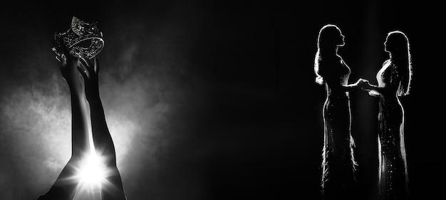 L'estratto della siluetta di due mani cerca di raggiungere la corona di diamanti mentre miss beauty queen pageant contest come competizione finale, il momento del vincitore finale tiene la mano insieme. spazio copia fumo retroilluminato