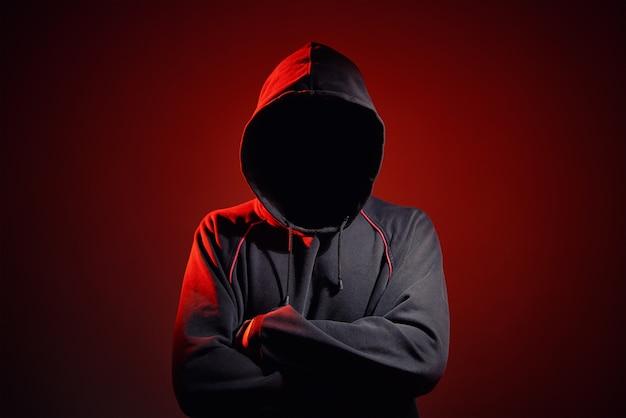 Sagoma un uomo senza volto nella cappa su uno sfondo rosso. anonimo concetto di criminalità