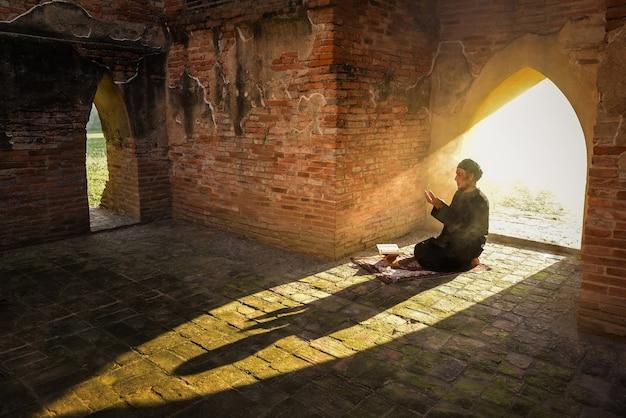 La sagoma di un uomo musulmano asiatico, che sta pregando in una stanza con la luce del sole che splende attraverso la porta della moschea