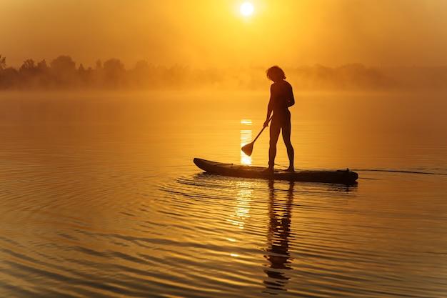 Sagoma di uomo atletico pagaiando a bordo di sup sul lago nebbioso durante l'alba incredibile.