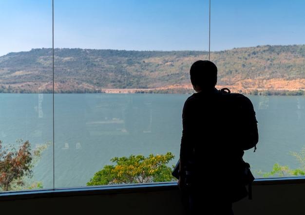 Sagoma sul retro dell'uomo turistico dello zaino in piedi e guardando dannazione e vista sulle montagne alla finestra trasparente dalla stanza interna, osservazione della diga di lamtakong a nakhon ratchasima, thailandia