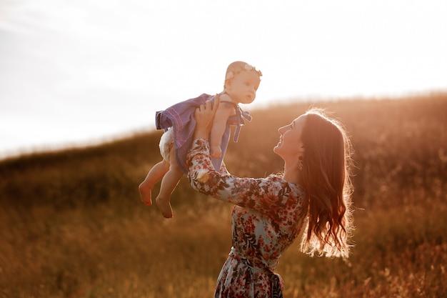La siluetta di bella donna solleva in alto la sua adorabile neonata a mezz'aria e la guarda sorridere.