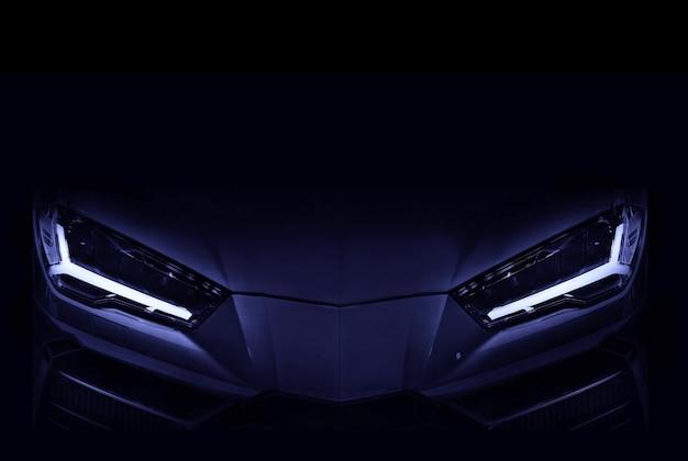 Sagoma di un'auto sportiva nera con fari a led su sfondo nero spazio copia