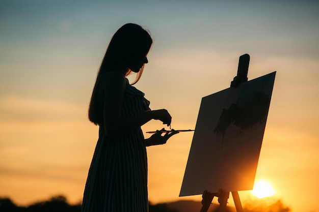 Sagoma di un artista ragazza bionda dipinge un dipinto sulla tela
