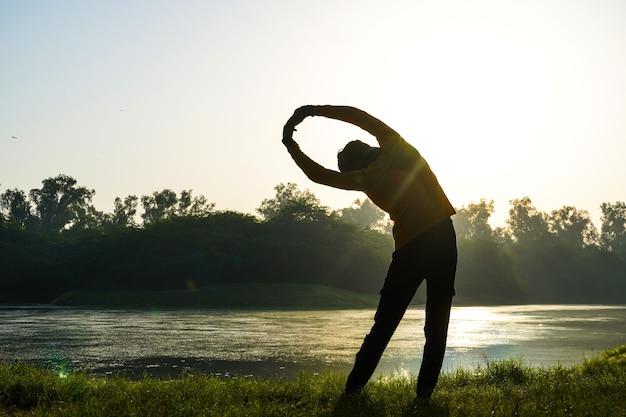 Silhouette di un ragazzo che fa esercizi nel parco vicino al sole e al fiume - concetto di salute