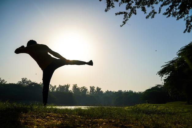 Silhouette di un ragazzo che fa pratica di taekwondo nel parco mattutino vicino al sole e al fiume