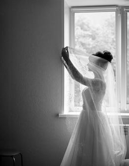 Sagoma della sposa aspettando lo sposo. ritratto in bianco e nero di una sposa elegante in piedi davanti a una finestra